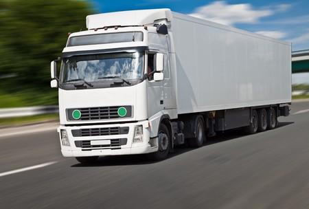 ciężarówka: BiaÅ'y ciężarówka na drogach, nieostry ruchu. Zdjęcie Seryjne