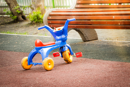 Abandoned colorful plastic childrens tricycle on the Playground