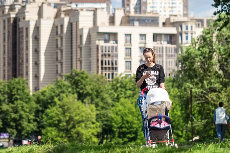 MOSCOW, RUSSIA - YULI 20, 2017: Unidentified young mother with a baby in a stroller. Editorial