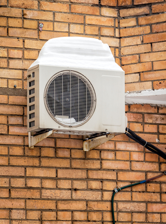 Air conditioner, installed on the wall of the house after winter snow.