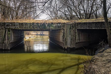 An old abandoned bridge over a small impure river. Stock Photo