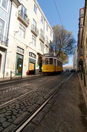 Yellow tram in Lisbon, Portugal. Small street in Alfama Stock Photo