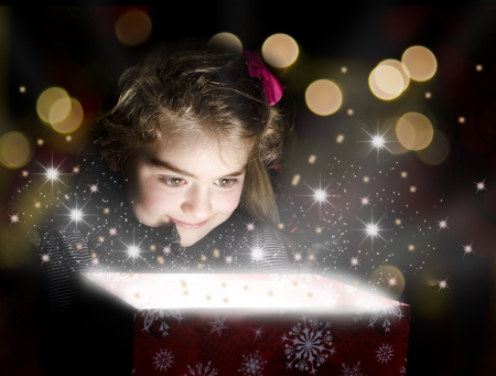 Child opening a magic gift box with lights and shining around Stock Photo - 16793293