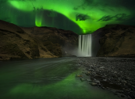 iceland: Flash of Aurora polaris above skogafoss waterfall, iceland Stock Photo
