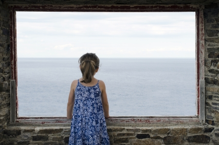 Lone little girl standing on window in front of the sea