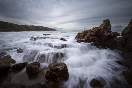 Little falls in the beach of Azkorri, Spain