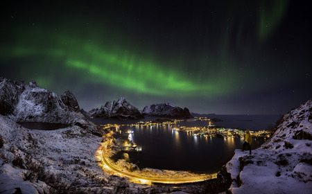 A man looking at the northern lights over Reine, Lofoten islands, Norway