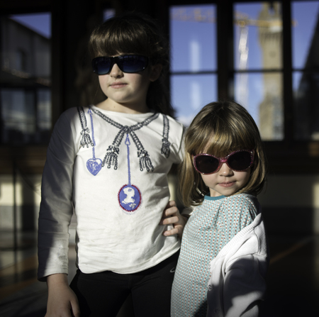 Two little models with sunglasses in a sunny day