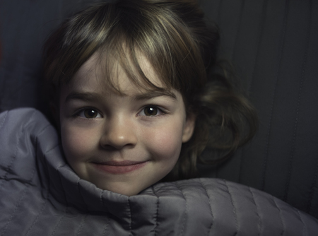 Smiling blonde little girl resting in her bed
