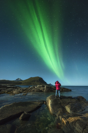 Woman taken pictures under the Northern Lights, Lofoten, Norway