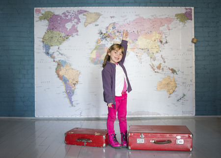 A traveller little girl smiling in front of a world map