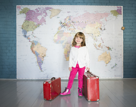A little girl smiling in front of a world map Stock Photo