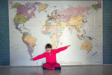 Little girl flying under a big World map