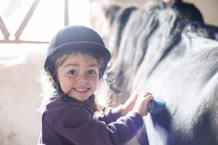 Little girl brushing her pony in the farm