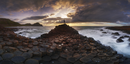 A woman on top of the old Giant's Causeway at sunset, Ireland