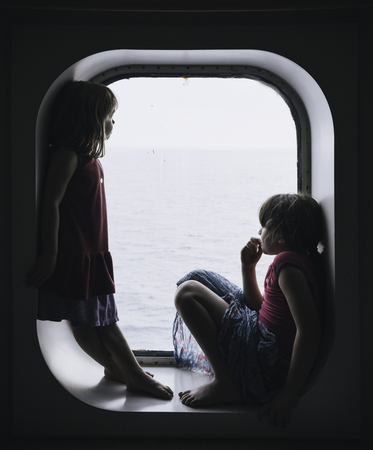 Two little girls looking the sea from a cruise window Stock Photo