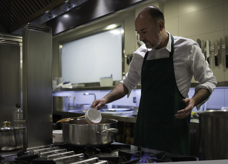 A chef, in his restaurant kitchen, cooking in the stove