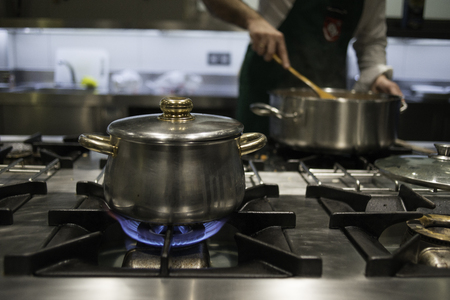 A chef in his kitchen cooking in the stove Stock Photo