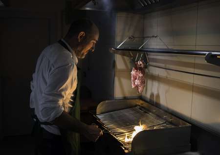 A chef cooking meat on fire in a restaurant