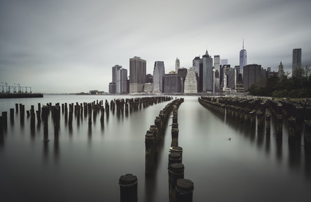 Mnahattan skyline from a Brooklyn`s shore old wooden pier Stock Photo