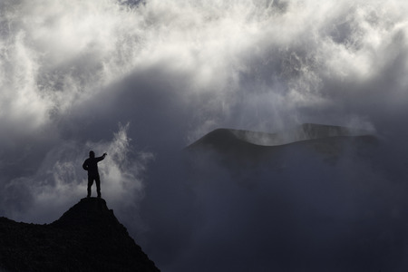 A mountanier man standing in front of a volcano in a cloudy day