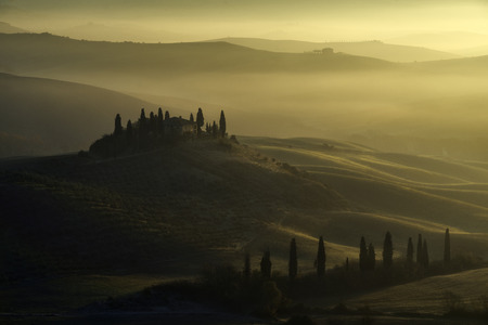 Sunrise over San Quirico D'orcia, Tuscany, in a misty morning of autumn
