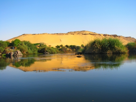 Reflection of a sand dune over the Nile river, Aswan, Egypt