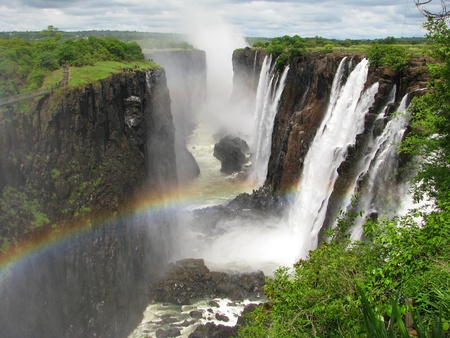 zambia: Rainbow over Victoria Falls on Zambezi River, border of Zambia and Zimbabwe