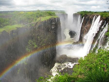 simbabwe: Regenbogen �ber Victoria Falls am Zambezi Fluss, Grenze zwischen Sambia und Simbabwe