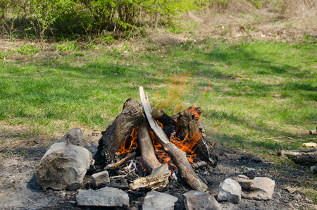 stone  fireplace: Fireplace of stone on green grass for baking bacon and sausages Stock Photo