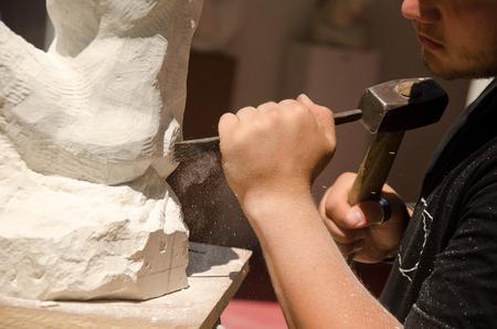 Uomo con il martello a lavorare su statua di pietra Archivio Fotografico