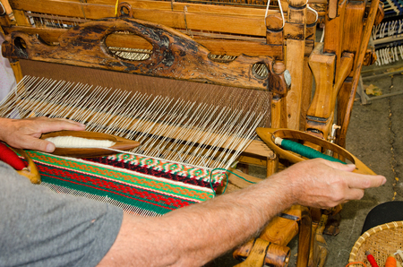 handloom: A man seated at a wooden handloom creating a handwoven woollen fabric Stock Photo