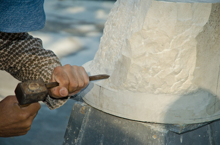 sculptor: Man with hammer working on stone statue Stock Photo