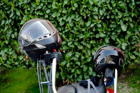 Moto helmet on motorcycle handlebars and motorbikes on blurred background Stock Photo