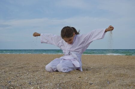 Kid practicing Aikido on the beach. Healthy lifestyle and sports concept