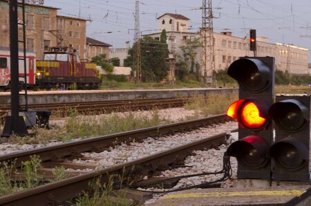 Railway signal with red light with railroad junction
