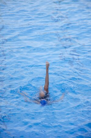Woman swimming in the swimming pool. Blue background.