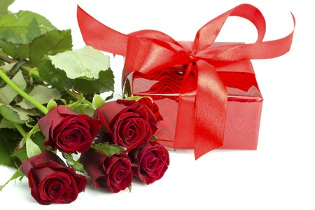 Bouquet of roses and red gift tied up by a bow on the white isolated background