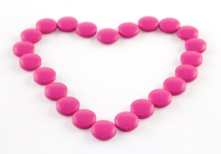 Pink tablets laid out in the form of heart on a white paper
