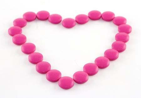 Roze tabletten in de vorm van hart aangelegd op een wit papier