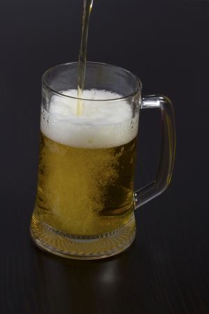 Pouring beer into a glass on the table photo