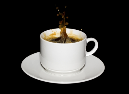 expresso: Sugar cube dropped into a cup of coffee isolated on a black background