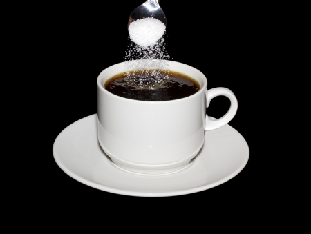 Sugar is poured from a spoon into a cup of coffee isolated on a black background photo