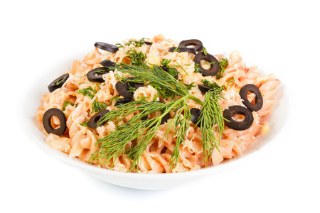 Pasta dish with tomato and olives on an isolated white background photo
