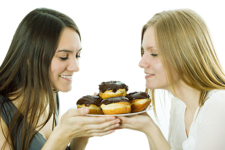 Girls hold cakes on a plate  and appetizingly at them look. The isolated background photo