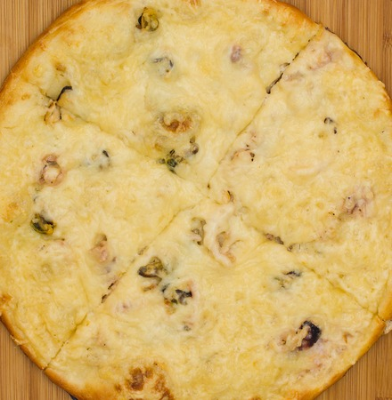 Appetizing ham, cheese and paprika pizza on a wooden tray photo