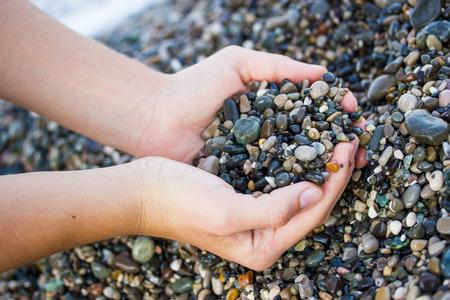 바다 돌을 들고 해변에있는 소녀