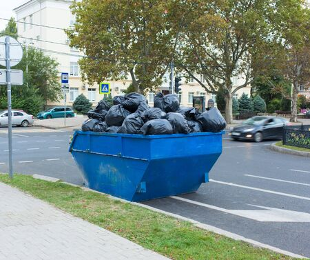A full dumpster with garbage bags stands on the street road