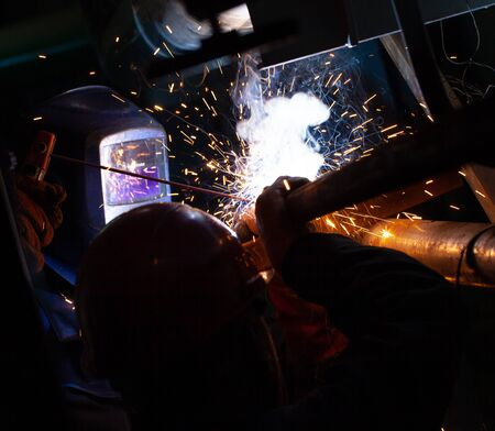 Electric welding works on the pipeline in a dark room Stock Photo