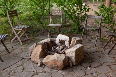 The fire area is fenced with stones. There are wooden chairs around